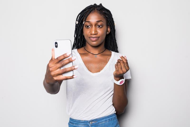 Νέα γυναίκα αφροαμερικάνων που παίρνει ένα selfie που απομονώνεται στο γκρίζο υπόβαθρο στοκ εικόνα