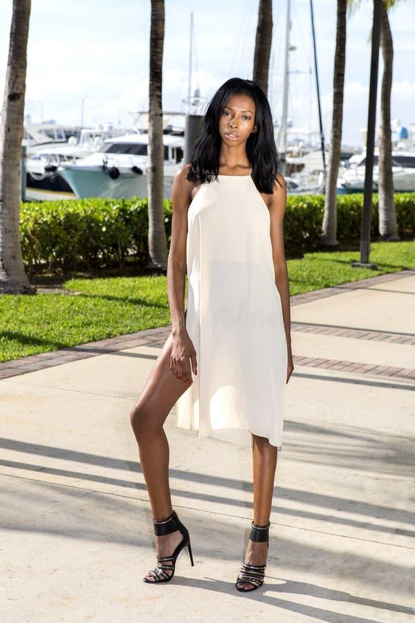 Νέα γυναίκα αφροαμερικάνων που περπατά, υπαίθρια Μαρίνα με τους φοίνικες στοκ εικόνες