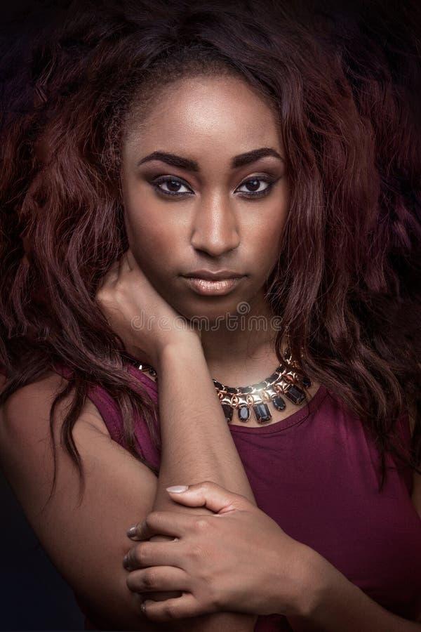 Νέα γυναίκα αφροαμερικάνων που φορά το κόκκινο φόρεμα στοκ φωτογραφία