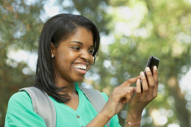 Νέα γυναίκα αφροαμερικάνων στο έξυπνο τηλέφωνο στοκ εικόνα