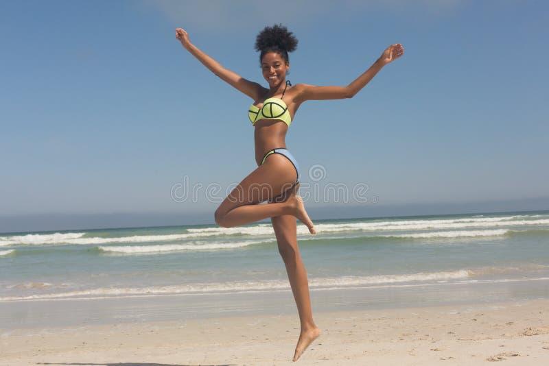 Νέα γυναίκα αφροαμερικάνων στο πράσινο μπικίνι που πηδά στην παραλία στοκ φωτογραφία με δικαίωμα ελεύθερης χρήσης