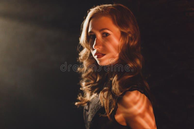 Νέα γυναίκα γοητείας που στέκεται στην ακτίνα ελαφριού και που φαίνεται κεκλεισμένων των θυρών στοκ φωτογραφία με δικαίωμα ελεύθερης χρήσης