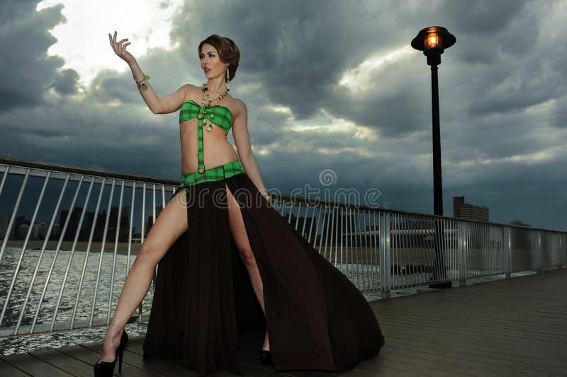 Νέα γυναίκα γοητείας στην αποβάθρα που φορά το επιπλέον φόρεμα θερέτρου μαγιό σχεδιαστών στοκ φωτογραφίες