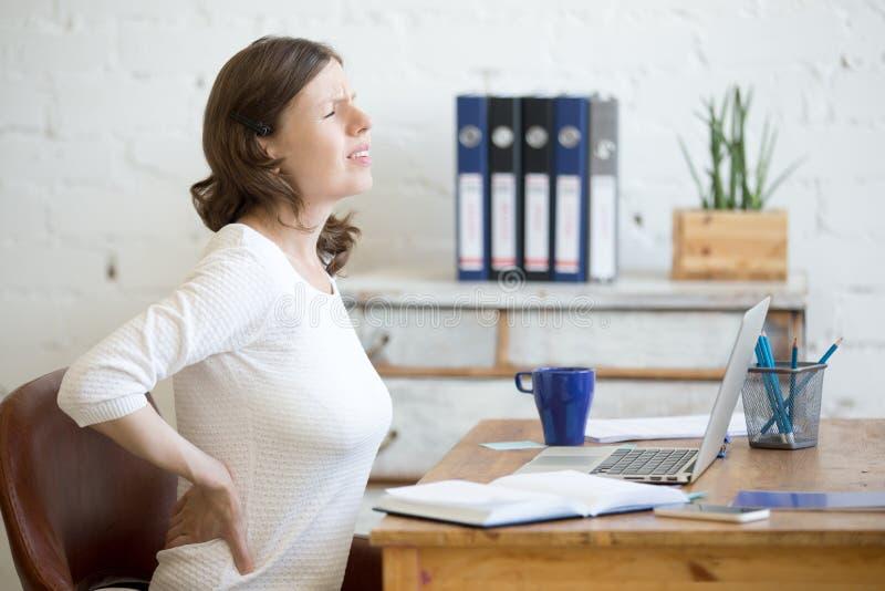 Νέα γυναίκα γραφείων που αισθάνεται τον πόνο στην πλάτη στοκ εικόνες με δικαίωμα ελεύθερης χρήσης