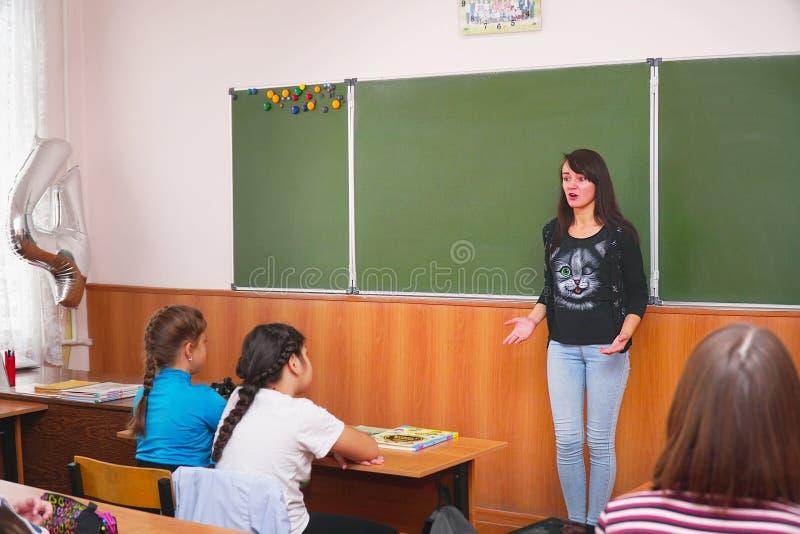 Νέα γυναίκα δασκάλων μπροστά από την κατηγορία στον πίνακα στοκ εικόνες