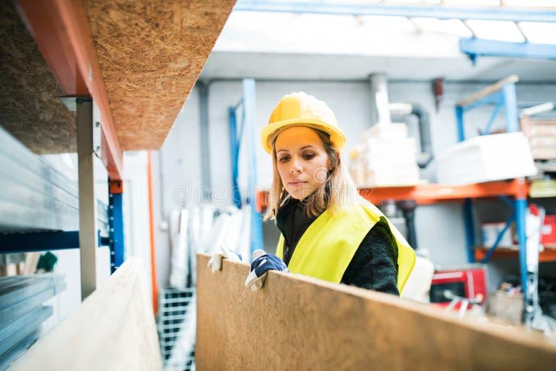Νέα γυναίκα εργαζόμενος σε μια αποθήκη εμπορευμάτων στοκ εικόνες