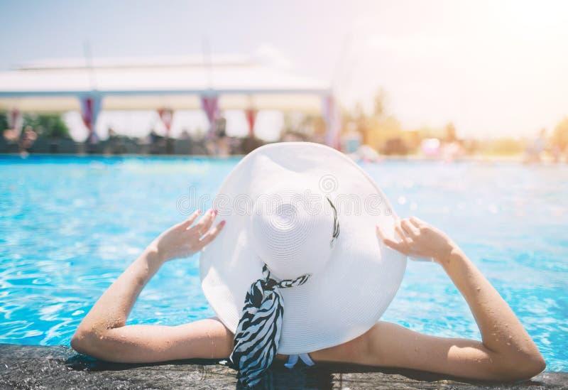 Νέα γυναίκα ευτυχής στη μεγάλη χαλάρωση καπέλων στην πισίνα, ταξίδι κοντά στην παραλία στο ηλιοβασίλεμα καλοκαίρι έννοιας στοκ εικόνες