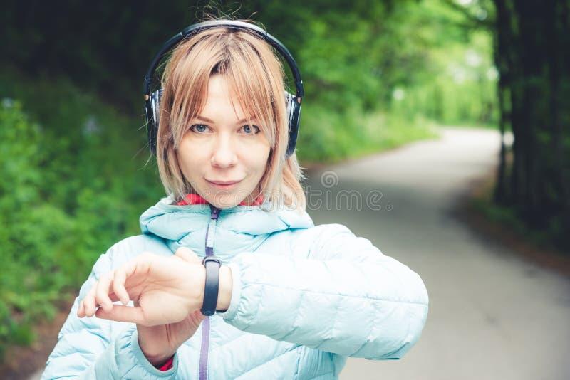 Νέα γυναίκα ικανότητας πορτρέτου που εξετάζει το έξυπνο ρολόι της παίρνοντας ένα σπάσιμο από την αθλητική κατάρτιση Έλεγχος φιλάθ στοκ εικόνες