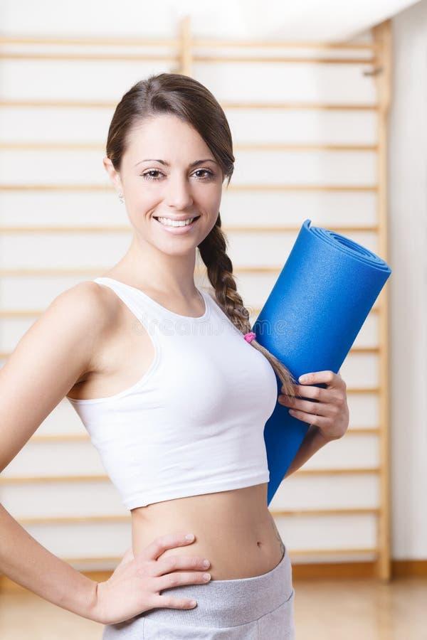Νέα γυναίκα ικανότητας που κρατά ένα μπλε χαλί στη γυμναστική στοκ φωτογραφία με δικαίωμα ελεύθερης χρήσης