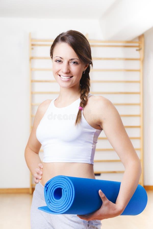 Νέα γυναίκα ικανότητας που κρατά ένα μπλε χαλί στη γυμναστική στοκ φωτογραφίες με δικαίωμα ελεύθερης χρήσης