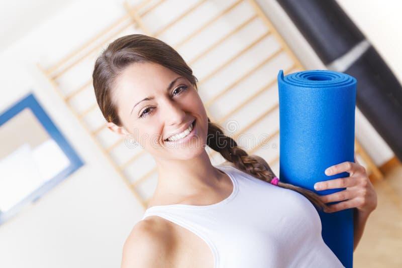Νέα γυναίκα ικανότητας που κρατά ένα μπλε χαλί στη γυμναστική στοκ εικόνες
