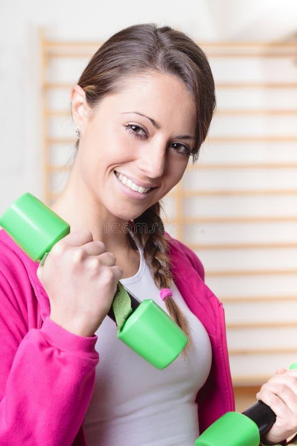 Νέα γυναίκα ικανότητας που χαμογελά και βάρη ανύψωσης στοκ εικόνα με δικαίωμα ελεύθερης χρήσης