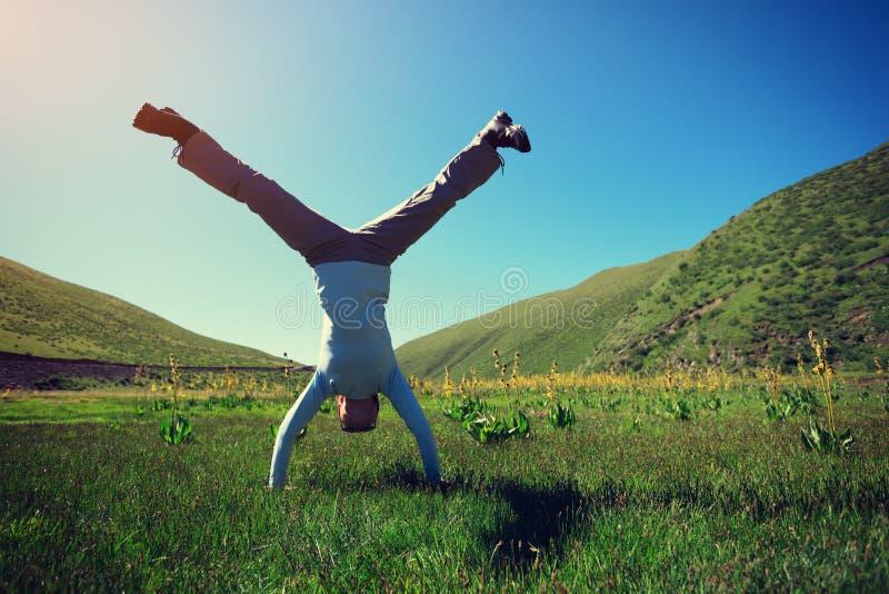 Νέα γυναίκα ικανότητας Handstand στο λιβάδι στοκ εικόνα
