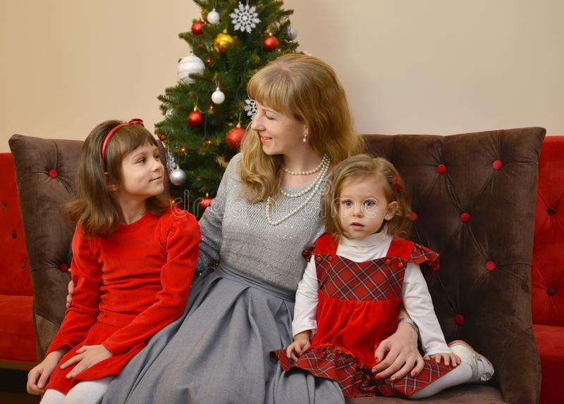 Νέα γυναίκα και δύο κορίτσια κάθονται στα πλαίσια ενός νέου δέντρου έτους στοκ φωτογραφία με δικαίωμα ελεύθερης χρήσης