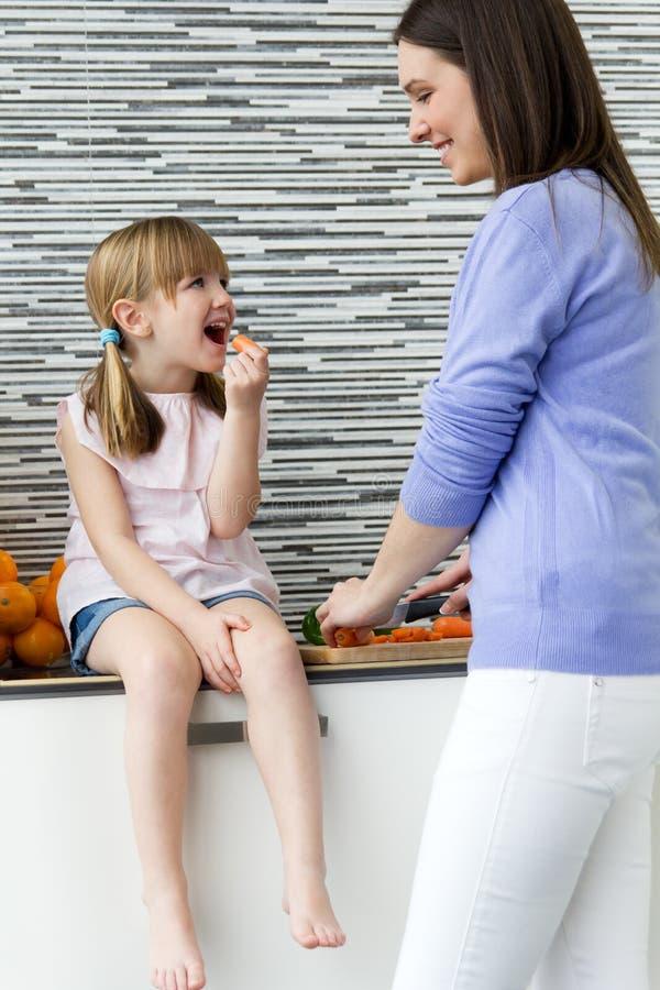 Νέα γυναίκα και μικρό κορίτσι που τρώνε τα καρότα στην κουζίνα στοκ εικόνα