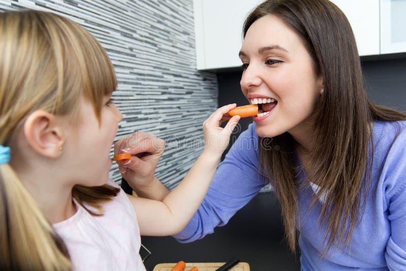 Νέα γυναίκα και μικρό κορίτσι που τρώνε τα καρότα στην κουζίνα στοκ φωτογραφίες με δικαίωμα ελεύθερης χρήσης