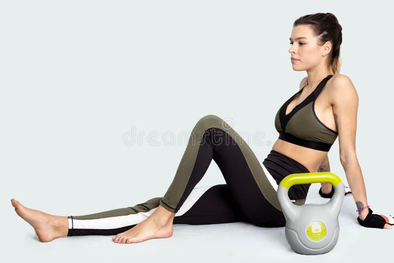 Νέα γυναίκα κατά τη διάρκεια ενός σπασίματος μετά από το workout με το kettlebell εικόνα στοκ φωτογραφίες με δικαίωμα ελεύθερης χρήσης