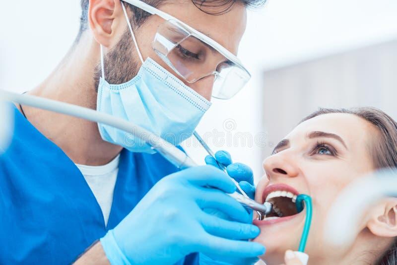Νέα γυναίκα κατά τη διάρκεια της ανώδυνης προφορικής επεξεργασίας σε ένα σύγχρονο οδοντικό γραφείο στοκ φωτογραφία με δικαίωμα ελεύθερης χρήσης