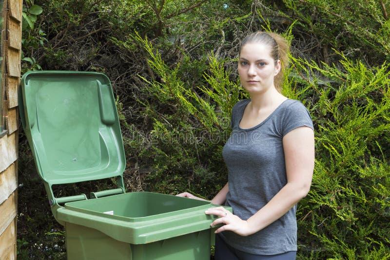 Νέα γυναίκα κοντά στο εμπορευματοκιβώτιο αποβλήτων στοκ εικόνες