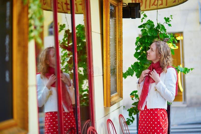 Νέα γυναίκα κοντά στο παρισινό παράθυρο εστιατορίων στοκ φωτογραφία με δικαίωμα ελεύθερης χρήσης