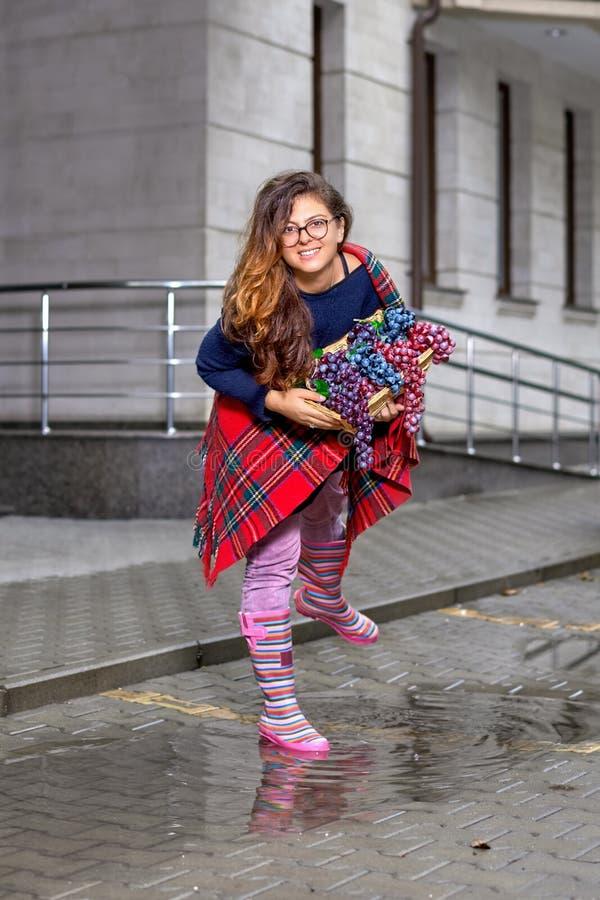 Νέα γυναίκα - κορίτσι με μακρυμάλλη στα γυαλιά, με ένα καλάθι των σταφυλιών, που χαμογελά ευτυχώς, στις λαστιχένιες μπότες που στ στοκ φωτογραφία με δικαίωμα ελεύθερης χρήσης