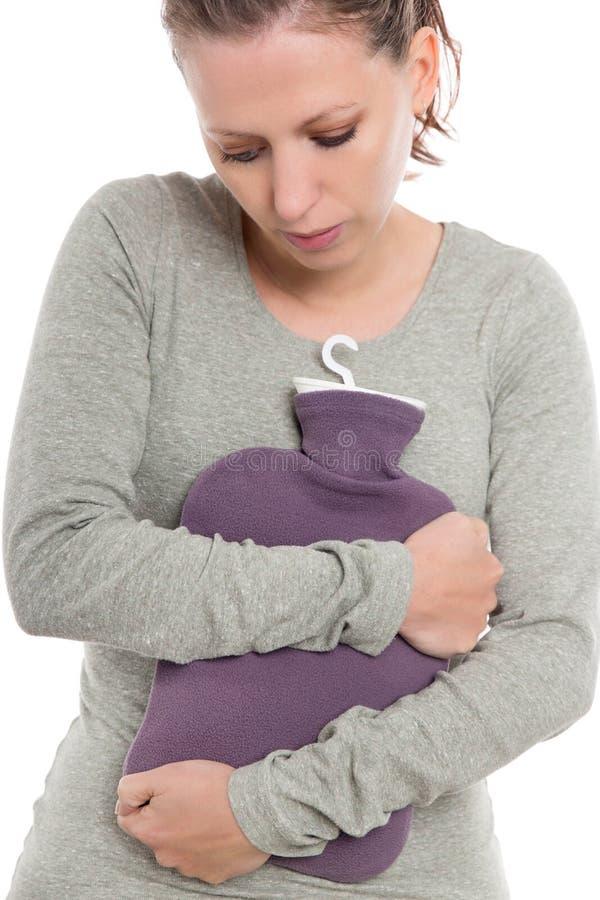 Νέα γυναίκα με έναν στομαχόπονο, έναν πόνο ή ένα abdominalgia στομαχιών, hottie και την τσάντα ζεστού νερού στοκ εικόνα