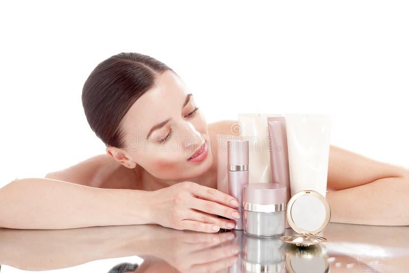 Νέα γυναίκα με ένα καλά-καλλωπισμένο δέρμα κοντά στα καλλυντικά κρεμών. στοκ φωτογραφίες με δικαίωμα ελεύθερης χρήσης