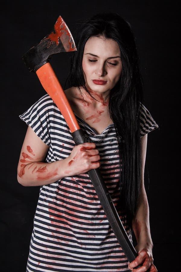 Νέα γυναίκα με ένα μεγάλο αιματηρό τσεκούρι στοκ φωτογραφία με δικαίωμα ελεύθερης χρήσης