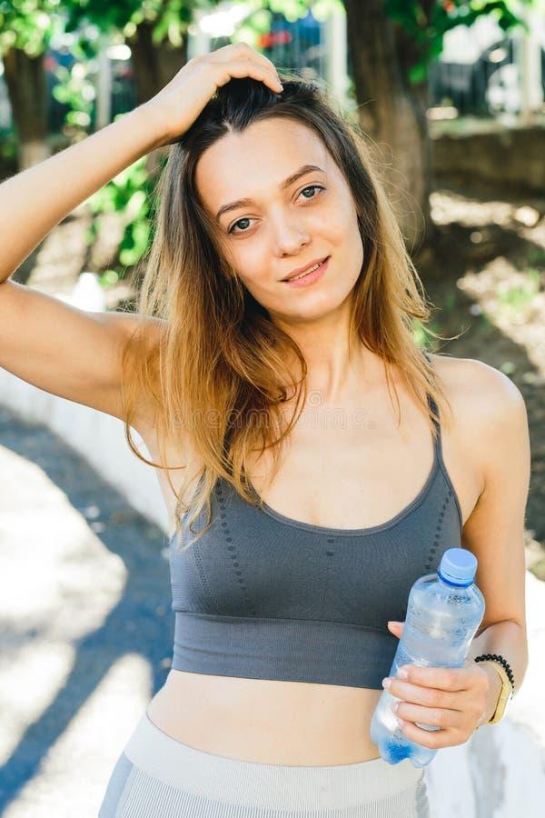 Νέα γυναίκα με ένα μπουκάλι νερό μετά από Jogging υπαίθρια στη Σιγκαπούρη στοκ εικόνες με δικαίωμα ελεύθερης χρήσης