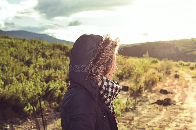 Νέα γυναίκα με ένα παλτό και μια κουκούλα επάνω στοκ εικόνες