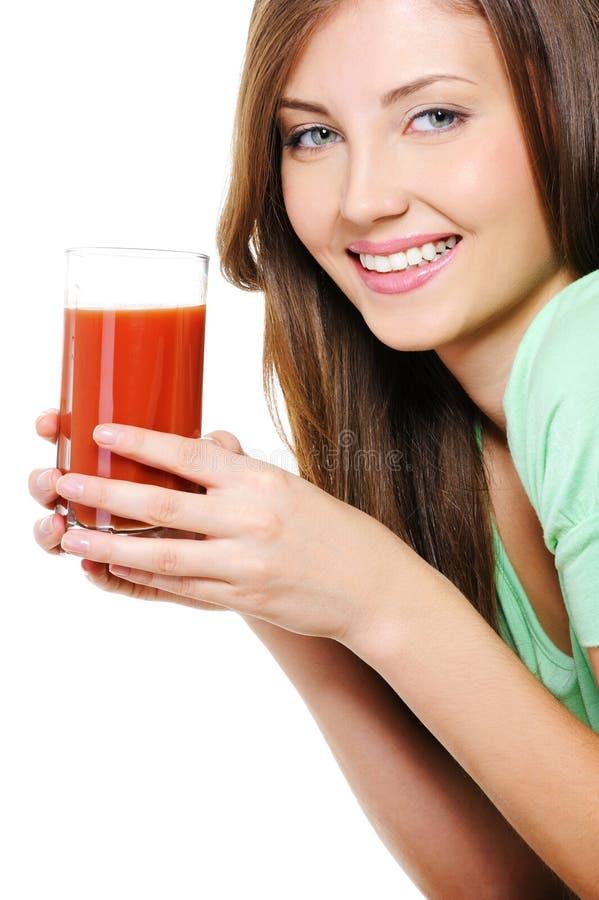 Νέα γυναίκα με ένα ποτήρι του χυμού ντοματών στοκ φωτογραφίες