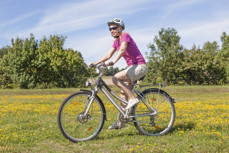 Νέα γυναίκα με ένα ποδήλατο στοκ εικόνες