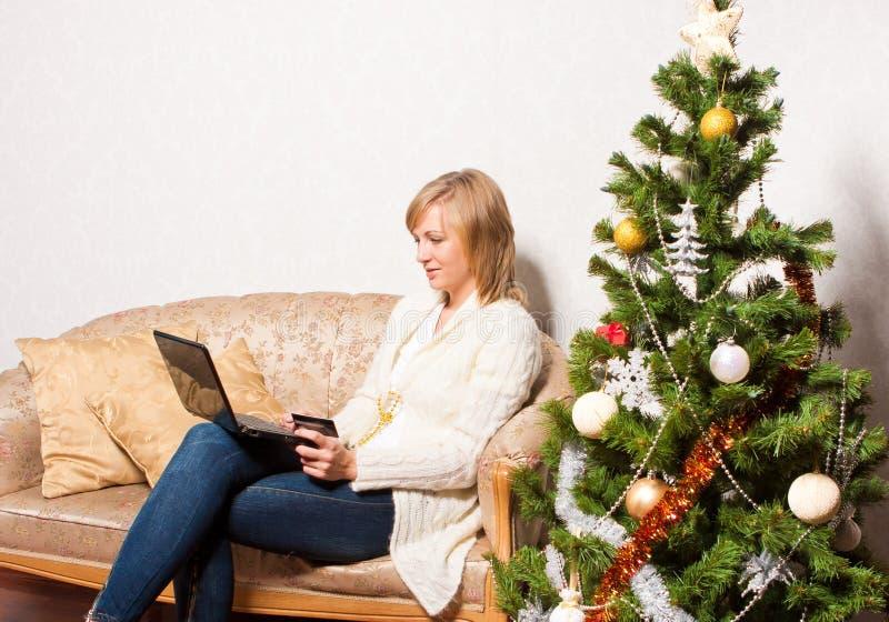Νέα γυναίκα με ένα σημειωματάριο κοντά στο χριστουγεννιάτικο δέντρο στοκ φωτογραφίες
