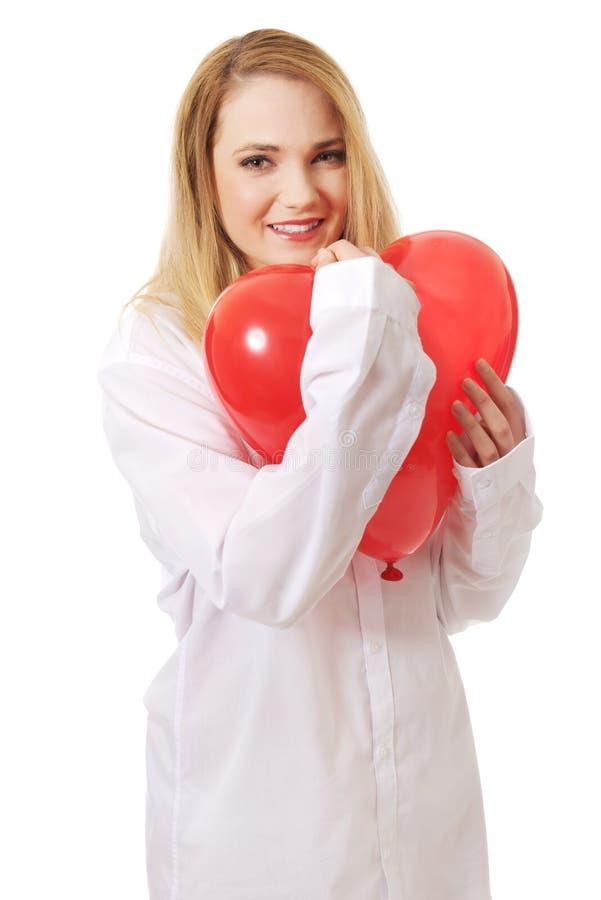 Νέα γυναίκα με διαμορφωμένο το καρδιά μπαλόνι στοκ φωτογραφία