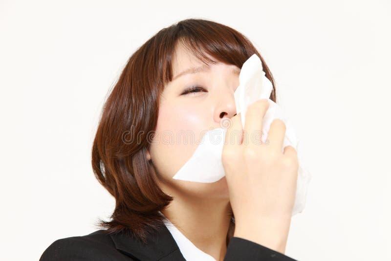 Νέα γυναίκα με μια αλλεργία που φτερνίζεται στον ιστό στοκ εικόνες