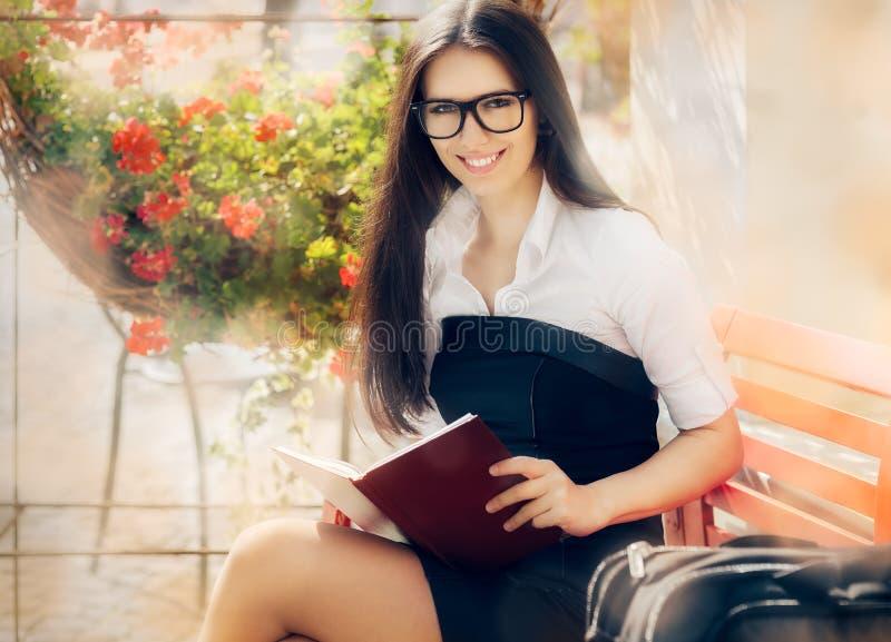 Νέα γυναίκα με μια συνεδρίαση βιβλίων σε έναν πάγκο στοκ εικόνες