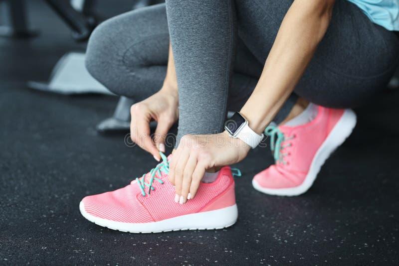 Νέα γυναίκα με τα δένοντας κορδόνια ιχνηλατών ικανότητας στη γυμναστική στοκ εικόνες