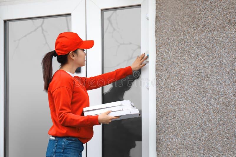 Νέα γυναίκα με τα κιβώτια πιτσών χαρτονιού που χτυπούν doorbell υπαίθρια Υπηρεσία παράδοσης τροφίμων στοκ εικόνες