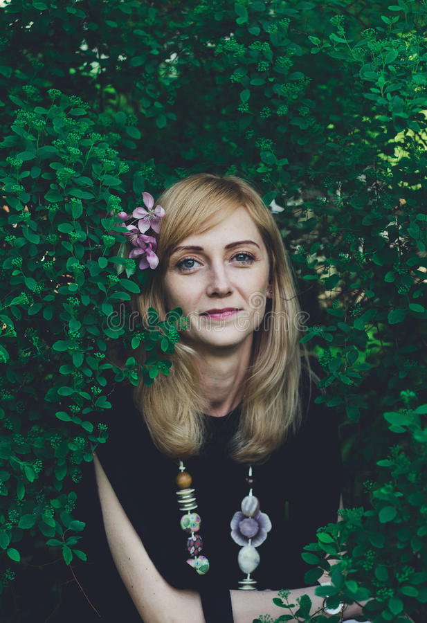 Νέα γυναίκα με τα λουλούδια στην τρίχα της που εξετάζει τη κάμερα στοκ φωτογραφίες