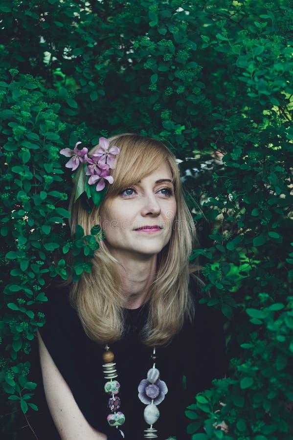 Νέα γυναίκα με τα λουλούδια στο λουλούδι hairwith της στην τρίχα της στοκ φωτογραφίες