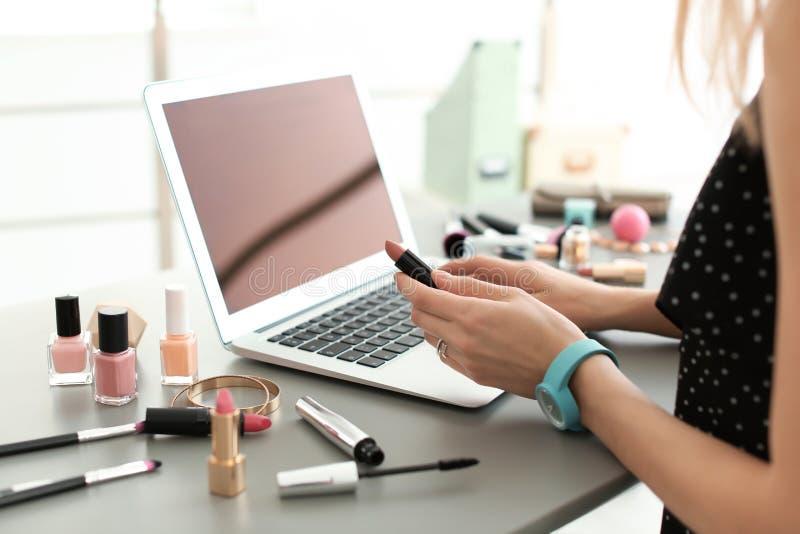 Νέα γυναίκα με τα προϊόντα makeup που χρησιμοποιούν το lap-top στον πίνακα στοκ φωτογραφίες