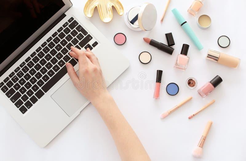 Νέα γυναίκα με τα προϊόντα makeup που χρησιμοποιούν το lap-top στοκ φωτογραφία