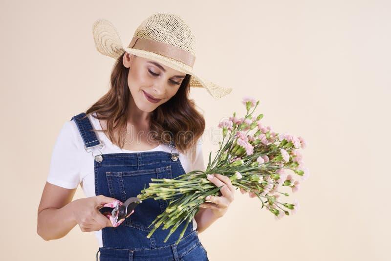 Νέα γυναίκα με τα τέμνοντα λουλούδια ψαλίδων περικοπής στοκ εικόνα με δικαίωμα ελεύθερης χρήσης