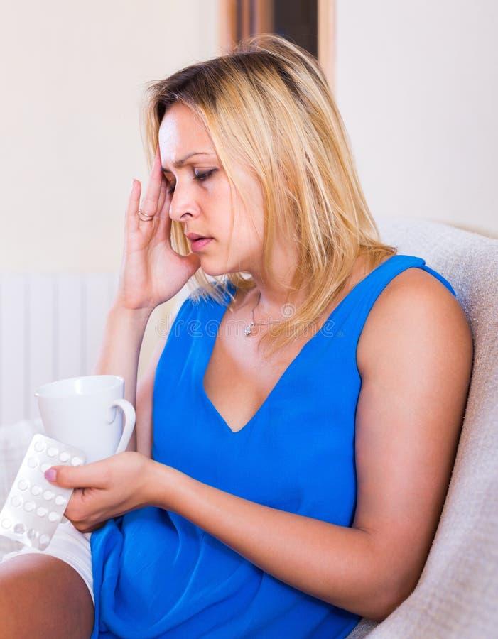 Νέα γυναίκα με τα χάπια στο σπίτι στοκ φωτογραφίες με δικαίωμα ελεύθερης χρήσης