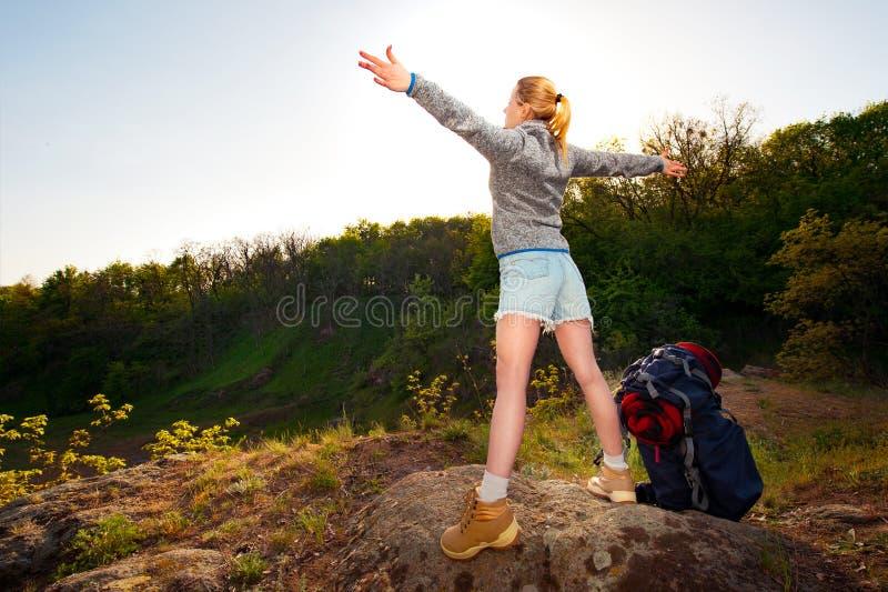 Νέα γυναίκα με τα χέρια που στέκονται επάνω στην κορυφή του En βουνών στοκ φωτογραφίες