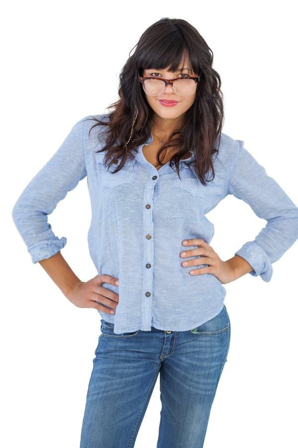 Νέα γυναίκα με τα χέρια της στα ισχία και τη φθορά των γυαλιών στοκ εικόνες με δικαίωμα ελεύθερης χρήσης