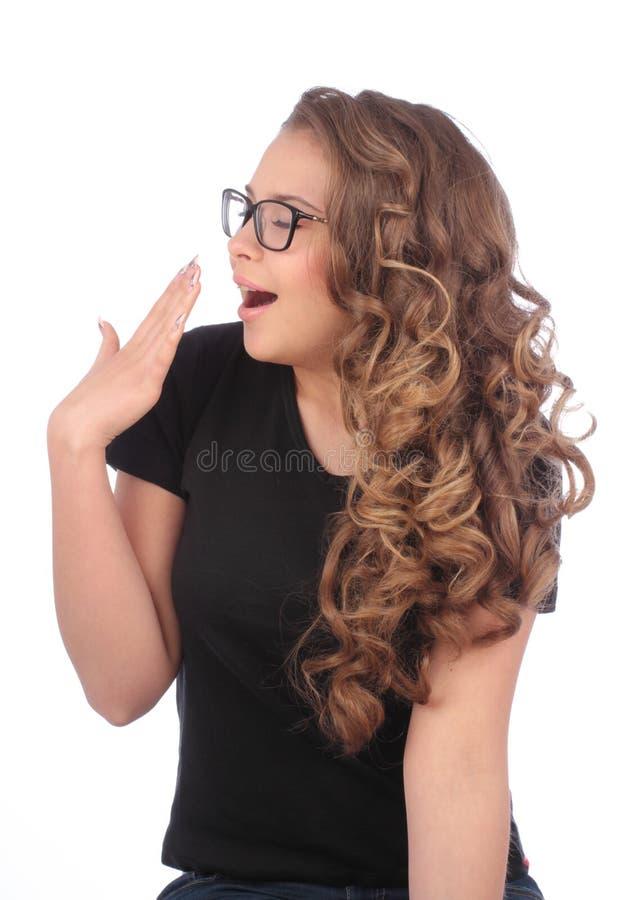 Νέα γυναίκα με τα χασμουρητά γυαλιών στο λευκό στοκ εικόνες με δικαίωμα ελεύθερης χρήσης