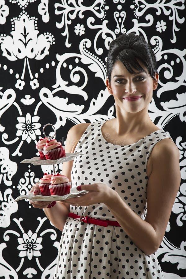 Νέα γυναίκα με τα cupcakes στοκ φωτογραφία