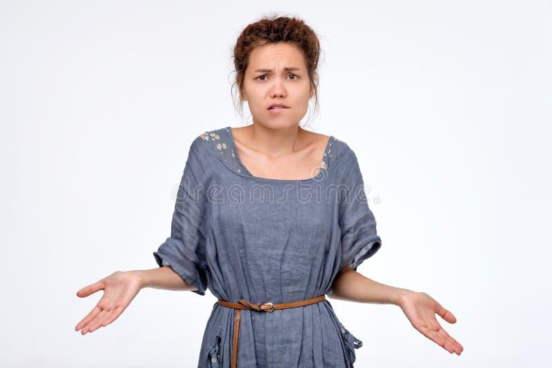 Νέα γυναίκα με τα dreadlocks που απαξιεί τους ώμους πέρα από το γκρίζο υπόβαθρο στοκ εικόνες