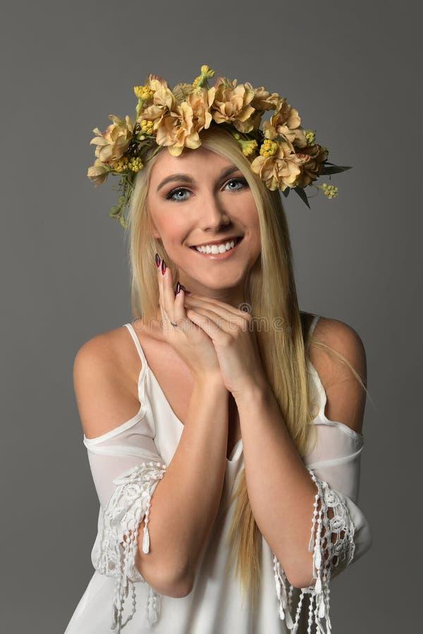 Νέα γυναίκα με την κορώνα των λουλουδιών στοκ εικόνα